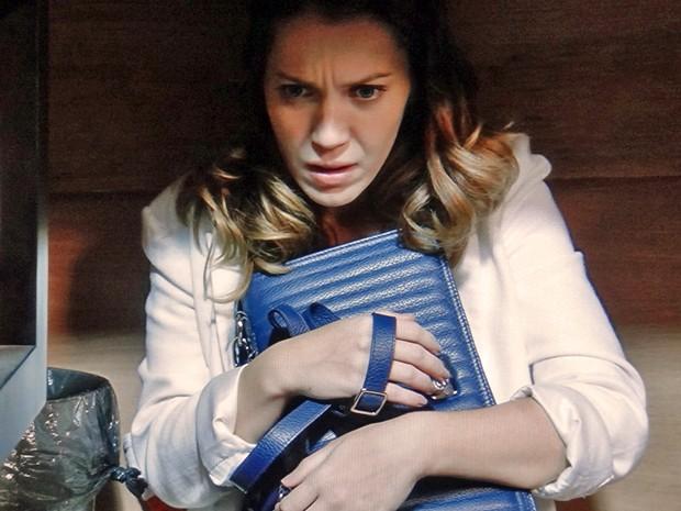 Laura se esconde em baixo da mesa ao ouvir que Marcos e Sueli entram na sala (Foto: TV Globo)