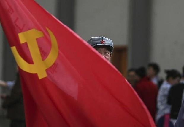 Homem carrega bandeira do Partido Comunista na China ; economia da China ; PIB da China ; economia chinesa ;  (Foto: Reuters)