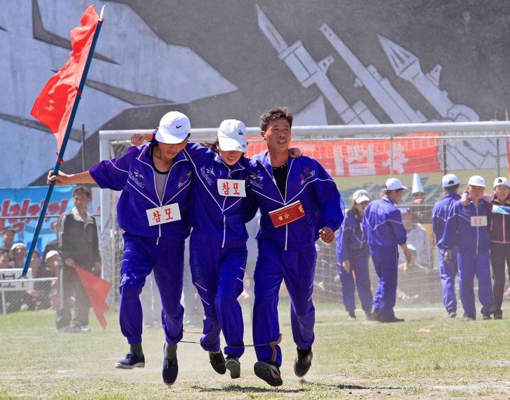 Com as pernas amarradas umas nas outras, homens participam de gingana em Pyongyang, na Coreia do Norte, para celebrar o Dia do Trabalhar nesta segunda-feira, dia 1º de maio de 2017 (Foto: Jon Chol Jin/AP)