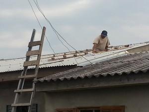 Homem conserta telhas em Eldorado do Sul, RS (Foto: André Azeredo/RBS TV)