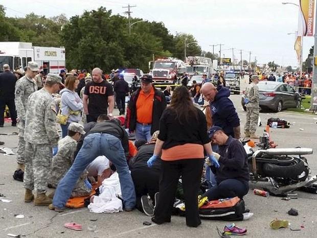 Pessoas socorrem vítimas de acidente em desfile universitário na cidade de Stillwater, em Okahoma, neste sábado (24) (Foto: REUTERS/David Bitton/Stillwater News Press)