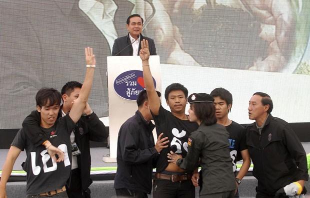 Estudantes são presos por fazerem o gesto do filme 'Jogos Vorazes' durante um discurso do primeiro-ministro da Tailândia, Prayuth Chan-ocha, nesta quarta-feira (19) (Foto: Bangkok Post/AP)