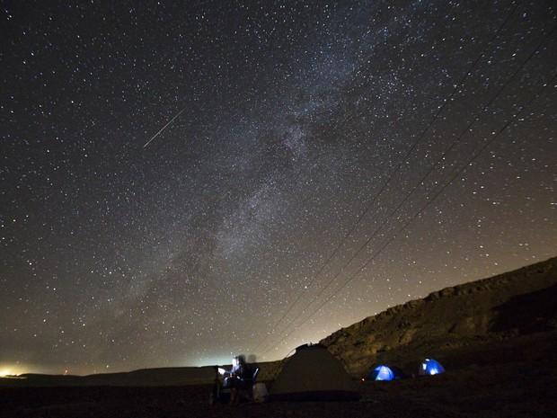 Pessoas acampam em lugar aberto à espera da chuva de meteoros Perseidas enquanto uma estrela cadente cruza o céu sobre Ramon Carter, em Israel. A mancha da Via Láctea também é vista no céu (Foto: Amir Cohen/Reuters)