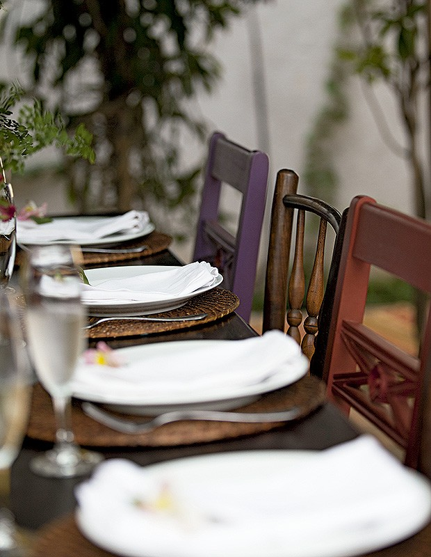 A mistura de cadeiras foi proposital, para uma dose de personalidade. No lugar de toalhas brancas, as mesas ganharam sousplats de rattan. Para cada guardanapo, uma flor  (Foto: Juliana Farinha / Editora Globo)