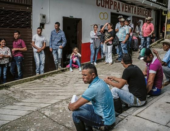 Camponeses aguardam a chegada do dinheiro em Briceno (Foto: Frederico Rios Escobar/ Época )