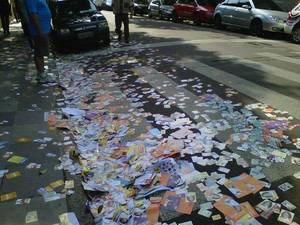Santinhos espalhados pela rua em frente ao Colégio das Dores, no centro de Porto Alegre (Foto: Cristine Gallisa/RBS TV)