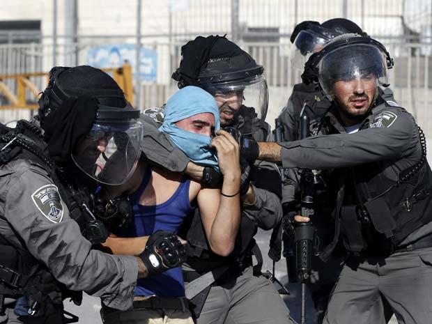 Policiais prendem palestino durante confronto nesta sexta-feira (18) perto do campo de refugiados de Shuafat, em Jerusalém (Foto: AFP PHOTO / AHMAD GHARABLI)