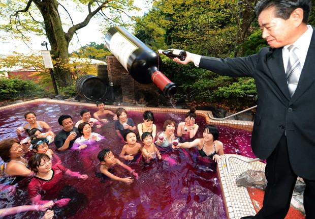 Sommelier Shunji Kanaya derruba um pouco mais do vinho na piscina, enquanto os visitantes se divertem e brindam ao vinho. (Foto: Toshifumi Kitamura/AFP)