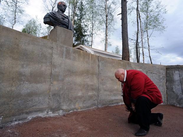 Homem se curva diante de busto do presidente russo Vladmir Putin, em Agalatovo, Rússia, neste sábado (16) (Foto: AFP PHOTO / OLGA MALTSEVA)