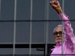 José Genoino ergue o braço à porta da sede da Polícia Federal de São Paulo, antes de se entregar para a prisão. Militantes de esquerda foram ao local para prestar apoio (Foto: Felipe Rau/Estadão Conteúdo)