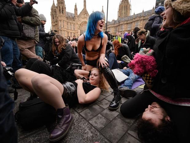 Dezenas de pessoas participam do protesto batizado de 'sentada na cara em massa' em frente ao Parlamento britânico em Londres, contra mudanças nas leis que regulam o consumo de pornografia (Foto: Leon Neal/AFP)