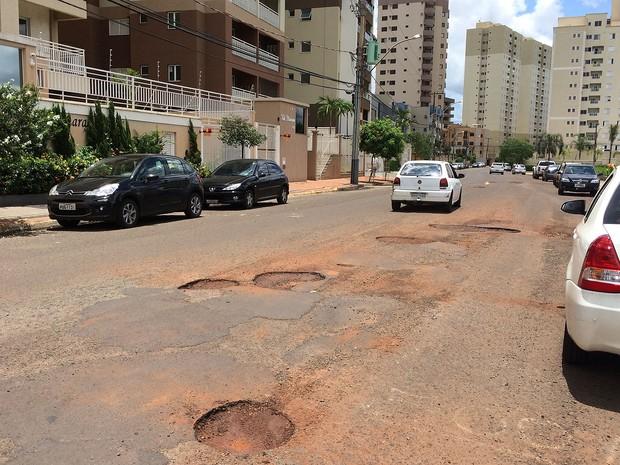 Motoristas precisam seguir na contramão para desviar de buracos na Rua Magda Perona Frossard, em Ribeirão Preto (Foto: Thaisa Figueiredo/G1)