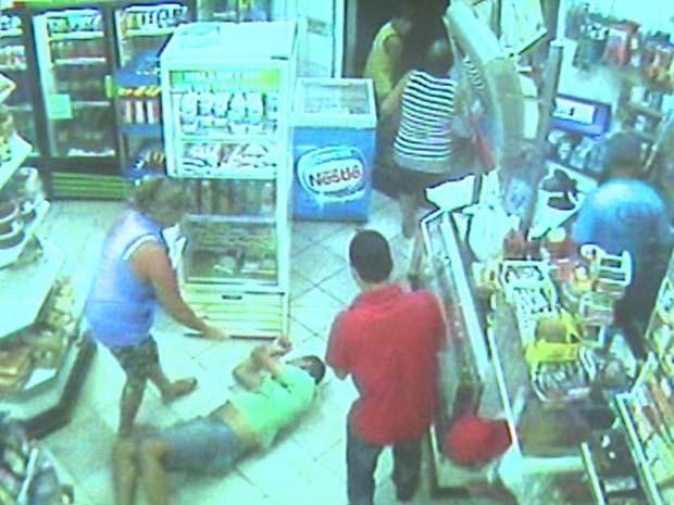 Homem cai no chão após levar dois tiros em padaria de Ribeirão (Foto: Reprodução/EPTV)