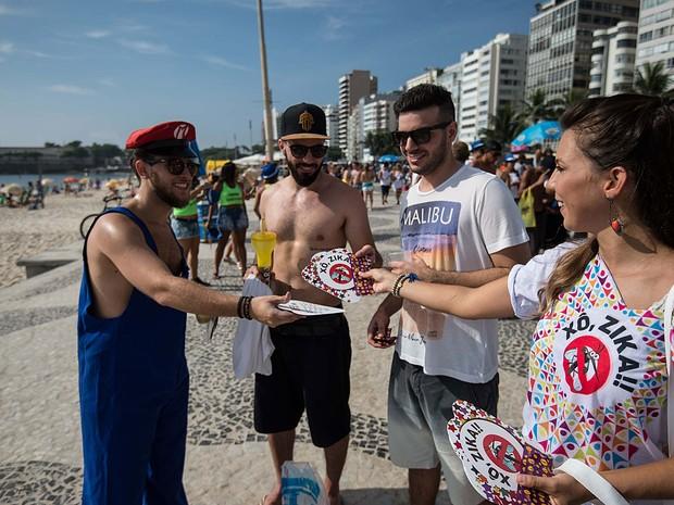 Agente municipal distribui cartilha educativa sobre o zika a turistas no Rio de Janeiro (Foto: Christophe Simon/AFP)