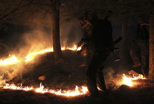 Membro do Exército Sírio Livre coloca fogo em área de Azaz nesta quarta-feira (31) (Foto: Asmaa Waguih/Reuters)