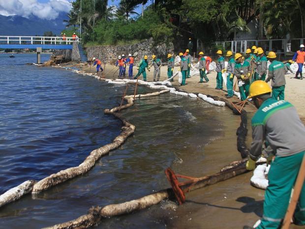 Funcionários da Petrobras trabalham na remoção de vazamento, em São Sebastião. (Foto: Jorge Mesquita/Estadão Conteúdo)