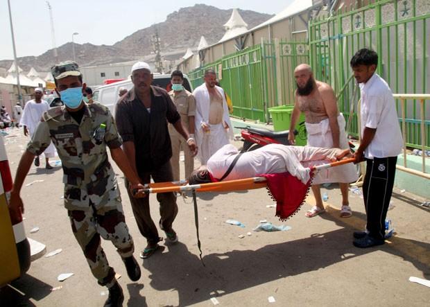 Homens carregam vítima de tragédia que deixou mais de 700 mortos na Arábia Saudita (Foto: STR / AFP)