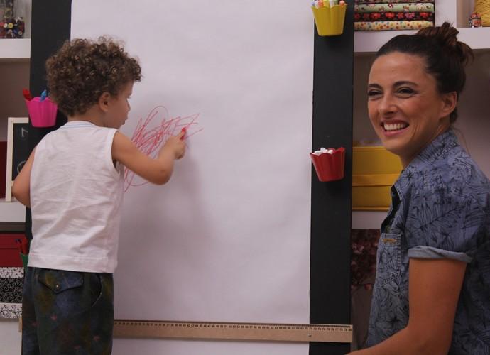 Kika Motta se diverte fazendo o suporte de pintura (Foto: Séries Originais/Gshow)