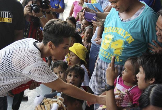 Alicia Keys toca crianças que sobreviveram à passagem do supertufão Haiyan nas Filipinas em visita a base aérea onde estão desabrigados nesta segunda (25) (Foto: Philippine Air Force/AP)