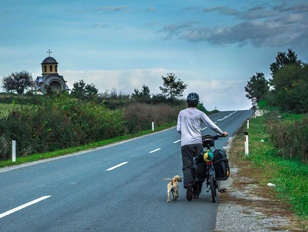 O administrador de redes Thiago Ruiz, de bicicleta e na companhia de um cachorro, na Sérvia (Foto: Diocá/Divulgação)