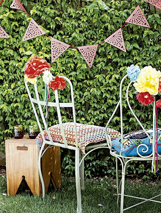 As bandeirinhas foram feitas no estilo mexicano, com efeito rendado, e as cadeiras ganharam muitas flores. Bandeirolas Parangolé, cadeiras Dom Mascate, almofada Botões de Amora (de crochê) e Westwing (bordada) (Foto: Elisa Correa/Editora Globo)
