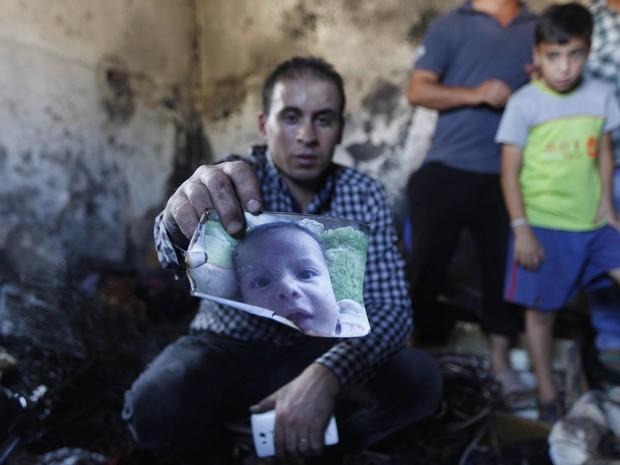 Homem mostra foto de um bebê palestino que morreu queimado e cujos pais ficaram feridos em estado grave em um ataque de colonos israelenses que atearam fogo a sua casa na Cisjordânia ocupada. O ato doi classificado como terrorista por Israel (Foto: Majdi Mohammed/AP)