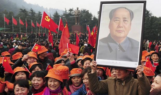Um homem segura um retrato de Mao Tsé-tung na data do 120º aniversário de nascimento do líder chinês. Milhares se reúnem em frente a uma estátua gigante de Mao na cidade natal dele. (Foto: Stringer/Reuters)