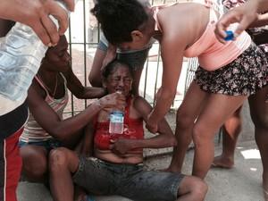 Moradora passa mal durante reintegação de posse de terreno no Rio (Foto: Guilherme Brito/G1)