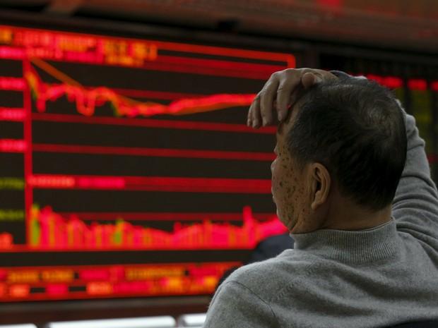 Homem observa painel eletrônico na bolsa de valores de Pequim, na China, nesta segunda-feira (4) (Foto: Kim Kyung-Hoon/Reuters)