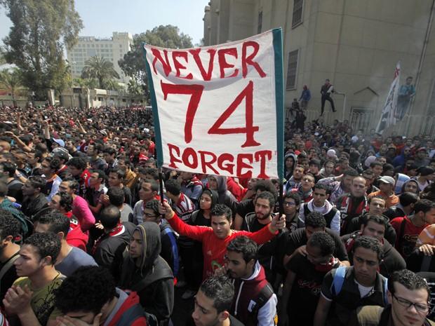 Manifestante segura cartaz em homenagem às 74 pessoas mortas em estádio (Foto: Amr Nabil/AP)
