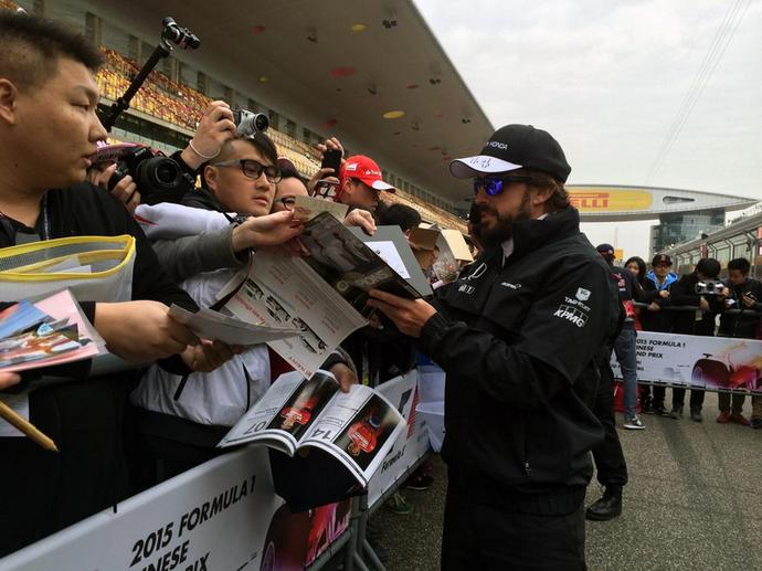 Fernando Alonso distribui autógrafos em Xangai, palco do GP da China (Foto: Divulgação)