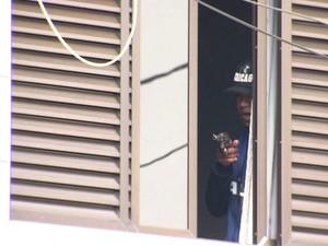 Criminoso apareceu diversas vezes na janela segurando uma arma (Foto: Reprodução / TV Tribuna)