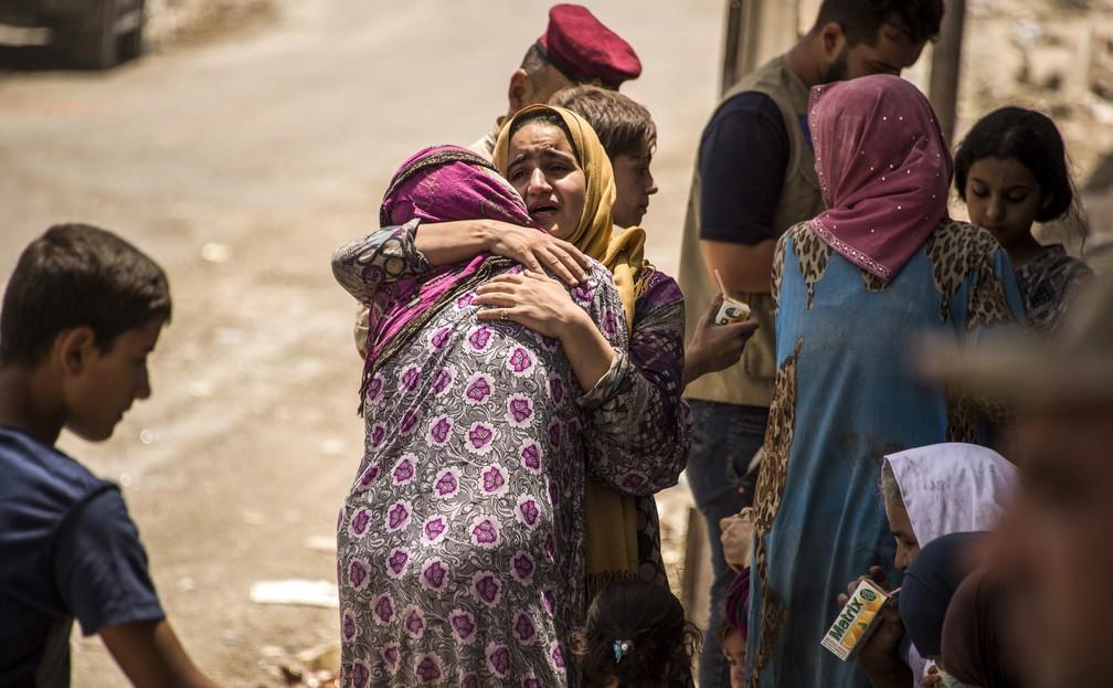 Mulheres se abraçam em Mossul, enquanto esperam para voltarem para suas casas após combate entre forças iraquianas e Estado Islâmico (Foto: Fadel SENNA / AFP)