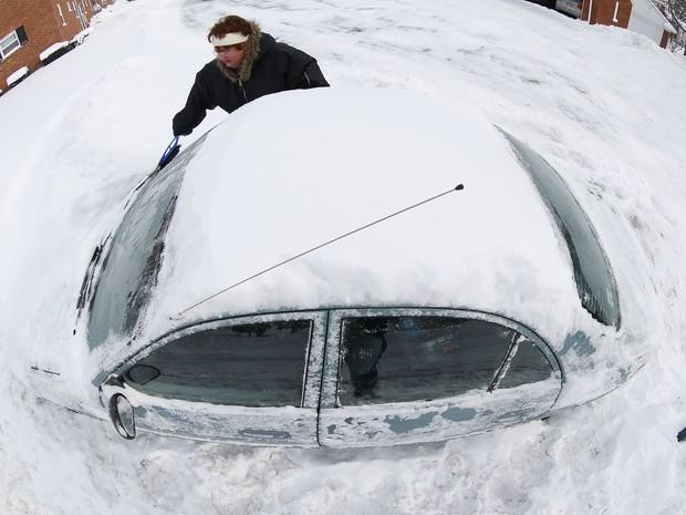 Em uma imagem feita com uma lente olho de peixe mulher tenta retirar neve acumulada em volta do seu carro em Grosse Pointe, Michigan. (Foto: Paul Sancya/AP)