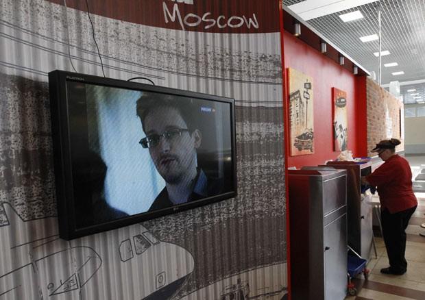 TV mostra imagem de Edward Snowden durante noticiário em café no aeroporto de Moscou nesta quarta-feira (26) (Foto: Sergei Karpukhin/Reuters)