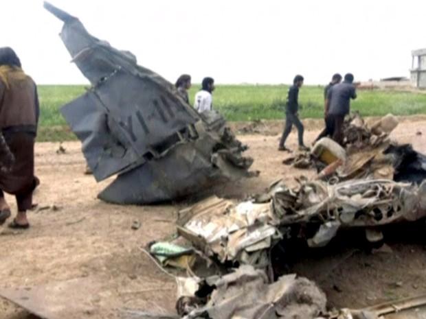 Imagem tirada de um vídeo postado em uma rede social extremistas mostra homens inspecionando o que o Estado Islâmico afirma ser os restos de um avião militar iraquiano em Hawija (Foto: Social Media Website/Reuters)