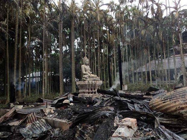 Estátua de Buda em meio às cinzas do templo de Lal Ching, em Ramu, Bangladesh, neste domingo (30) (Foto: AFP)