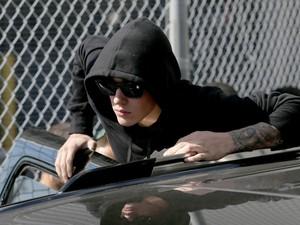 Justin Bieber sai do carro para acenar para fãs e jornalistas (Foto: Joe Raedle/Getty Images/AFP)