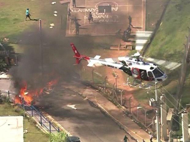 Helicóptero da Polícia Militar sobrevoa barricada em chamas feita por moradores que protestam contra reintegração em Itaquera, na Zona Leste (Foto: Reprodução / Globo News)