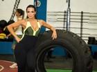 Carla Prata usa macacão decotado e pega pesado na malhação