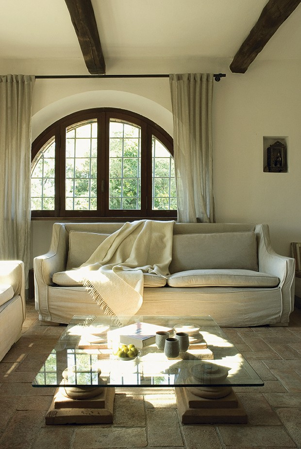 Pela sala de estar, que tem janelas em arco, pode-se acessar o pátio dos fundos desta casa, que fica na região italiana da Toscana (Foto:  Brando Cimarosti / Casa e Jardim)