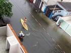 Homem pratica stand up paddle em rua alagada no litoral de SP
