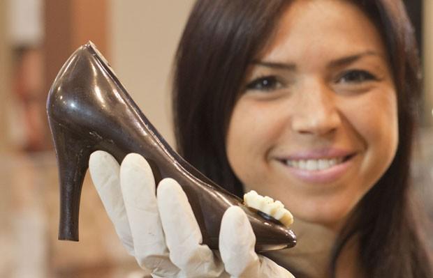 Jovem mostra guloseima na forma de sapato. (Foto: Carlo Hermann/AFP)