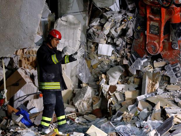 Bombeiro trabalha nas ruínas de uma casa que desmoronou após o terremoto em Amatrice, na Itália, na quarta (24) (Foto: Reuters/Stefano Rellandini)