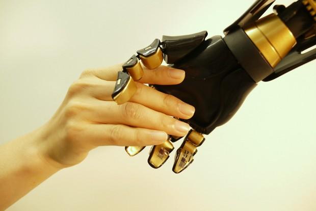 Mão humana aperta mão robótica com mecanorrecptores artificiais  (Foto: Bao Research Group/Stanford University)