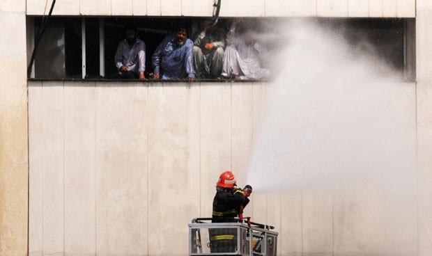 Bombeiro joga água para tentar controlar as chamas e amenizar o calor entre as pessoas encurraladas no prédio (Foto: Arif Ali/AFP)