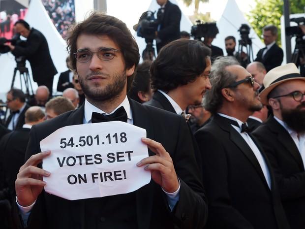 Humberto Carrão, ator do filme 'Aquarius', protesta no tapete vermelho do Festival de Cannes, na terça-feira (17) (Foto: ANNE-CHRISTINE POUJOULAT/AFP)