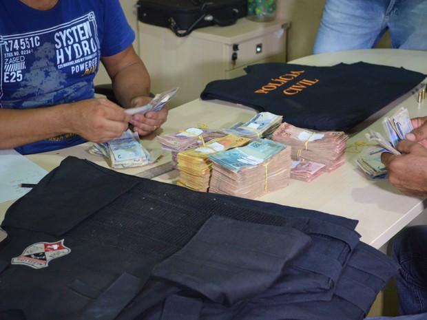 Com os suspeitos foram apreendidos uma arma e uma grande quantidade de dinheiro. (Foto: Rogério Aderbal/G1)