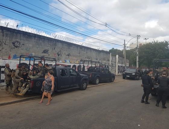 Moradora passa por policiais militares durante operação no Complexo da Maré nesta quinta-feira (Foto: Hudson Corrêa)