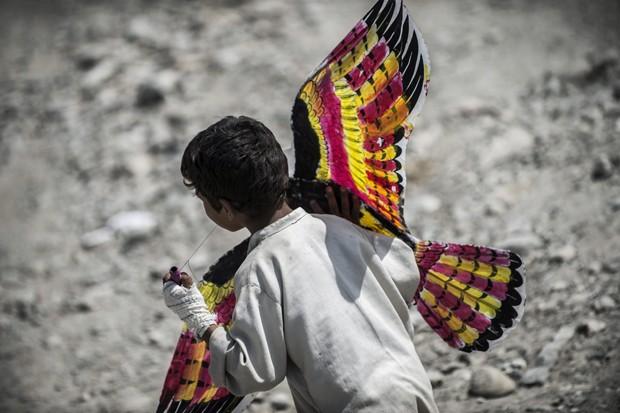 Menino brinca com sua pipa em Naghlu (Foto: JEFF PACHOUD/AFP)